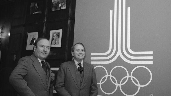 Герберт Шлоссер (справа) и Роберт Ховард позируют на фоне эмблемы Олимпиады-80 - Sputnik Latvija