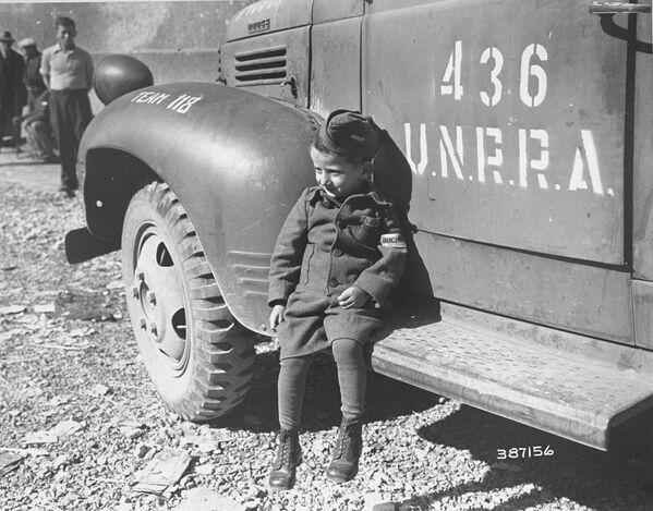 Четырехлетний бывший узник лагеря Бухенвальд около машины UNRRA, 1945 год - Sputnik Латвия