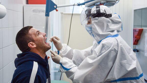 Сотрудник медицинской службы аэропорта Шереметьево проводит экспресс-тестирование на COVID-19 для пассажиров системой EMG - Sputnik Latvija