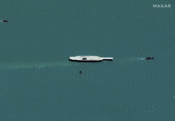 ASV aviācijas bāzes kuģa makets aiz velkoņa Irānas militārajās mācībās Ormuza šaurumā - Sputnik Latvija