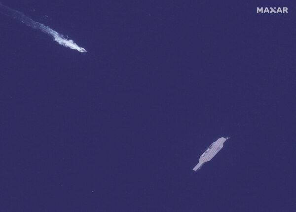 ASV aviācijas bāzes kuģa makets un ātrgaitas kuteris, kas tuvojas no Bandarabasas Ormuza šaurumā  - Sputnik Latvija