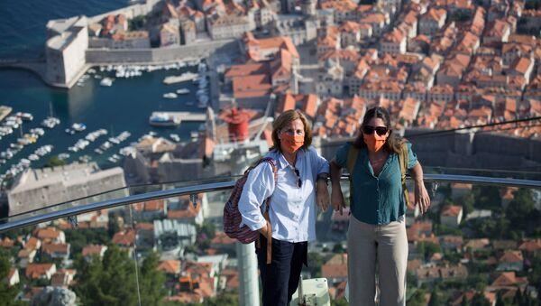 Туристы в защитных масках позируют на верхней станции канатной дороги над старым городом Дубровником в Хорватии - Sputnik Латвия