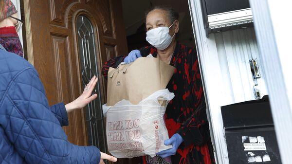 Волонтер передает пакет с продуктами - Sputnik Латвия