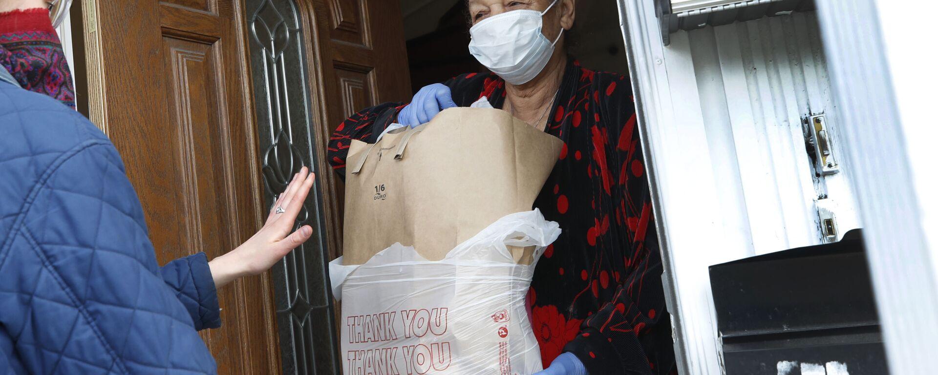 Волонтер передает пакет с продуктами - Sputnik Latvija, 1920, 29.11.2020