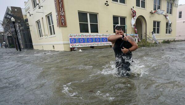 Мужчина на затопленной улице города Пенсакола в штате Флорида во время урагана Салли - Sputnik Латвия