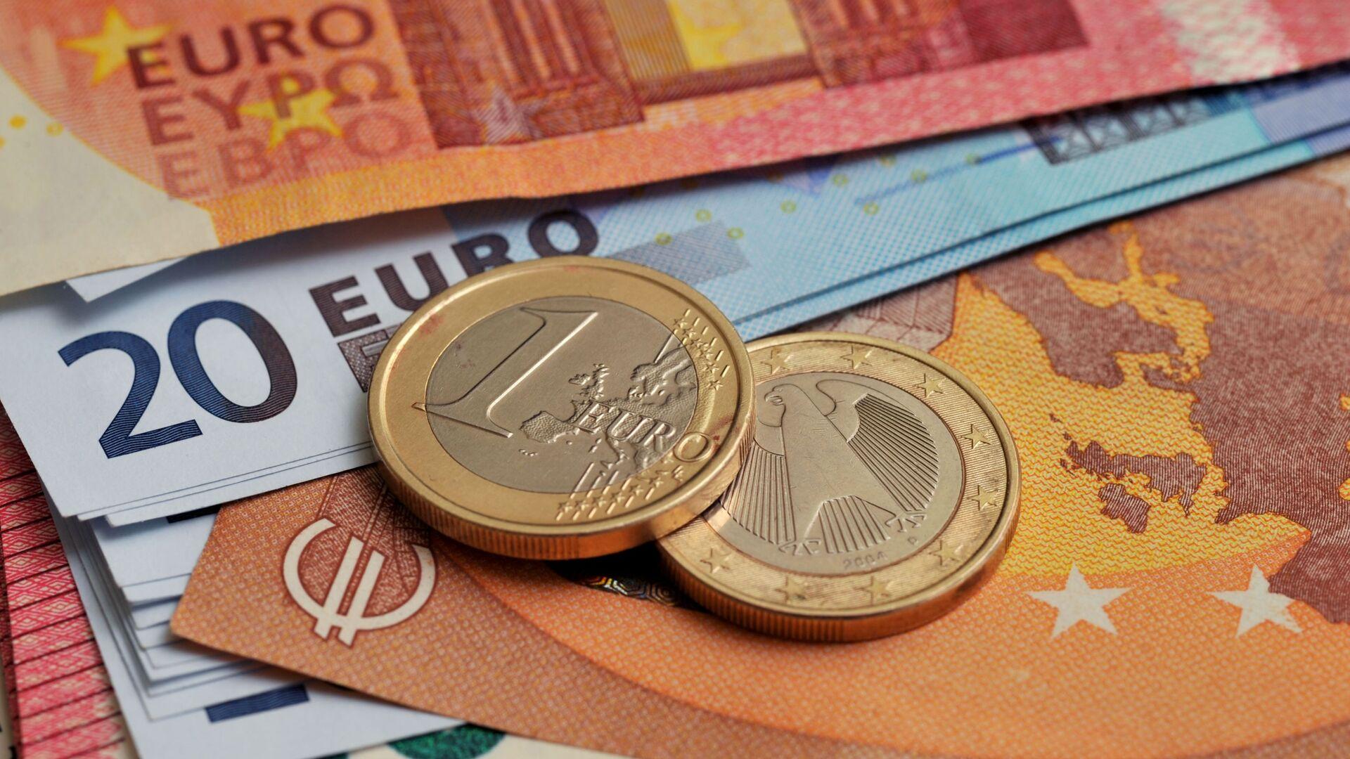 Монеты номиналом 1 евро на фоне банкнот номиналом 10 и 20 евро - Sputnik Latvija, 1920, 08.04.2021