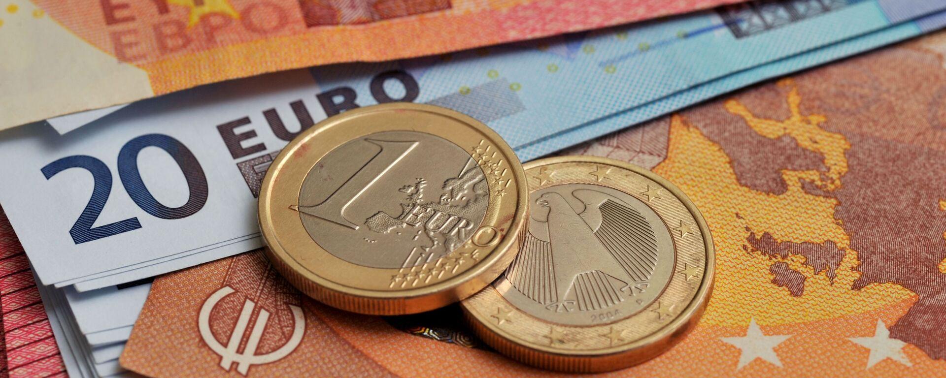 Монеты номиналом 1 евро на фоне банкнот номиналом 10 и 20 евро - Sputnik Латвия, 1920, 14.09.2021