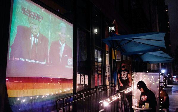 Трансляция первых дебатов действующего президента США Дональда Трампа и кандидата в президенты США Джо Байдена на мониторе у входа в бар в верхнем Вест-Сайде в Манхэттене - Sputnik Латвия