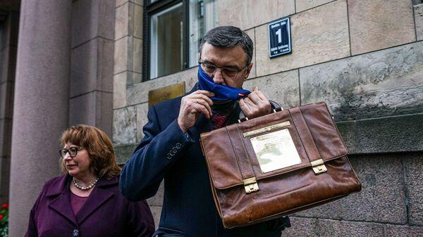 Министр финансов Янис Рейрс несет портфель с проектом бюджета на 2021 год - Sputnik Латвия