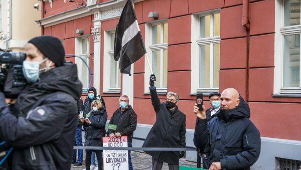 Протестующий поднимает флаг Латвии в траурной расцветке - Sputnik Латвия