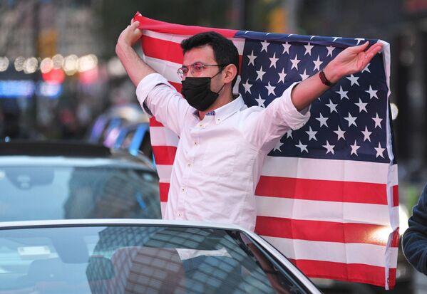 Человек с флагом США на Таймс-сквер в Нью-Йорке после новостей о победе на выборах президента США кандидата от Демократической партии Джозефа Байдена - Sputnik Латвия