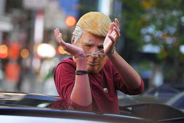 Человек в маске Дональда Трампа едет на машине по улице Нью-Йорка после новостей о победе на выборах президента США кандидата от Демократической партии Джозефа Байдена - Sputnik Латвия