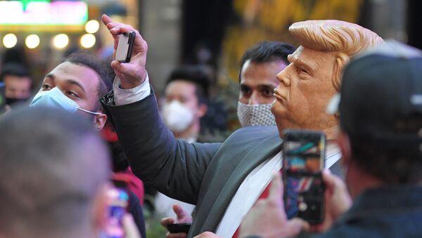 Люди на Таймс-сквер в Нью-Йорке фотографируют человека в маске Дональда Трампа - Sputnik Латвия
