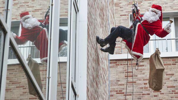 Спасатель в костюме Санты-Клауса спускается с крыши детской больницы в Германии  - Sputnik Latvija