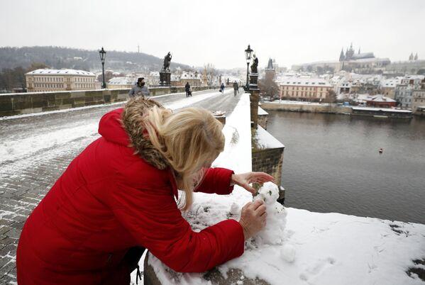 Женщина лепит снеговика на Карловом мосту в Праге, Чехия - Sputnik Latvija