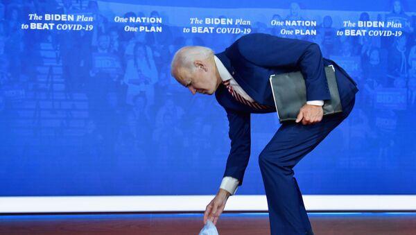 Кандидат в президенты США Джо Байден наклоняется за упавшей медицинской маской - Sputnik Latvija