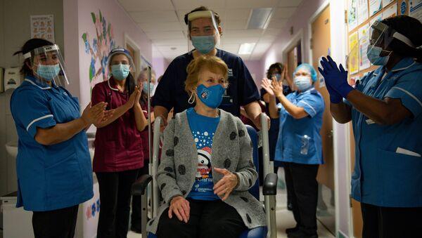 Персонал больницы аплодирует Маргарет Кинан, которая первой в Британии вакцинировалась от COVID-19 - Sputnik Латвия