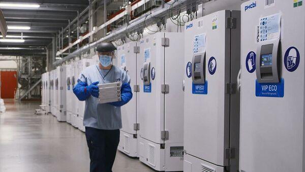 Сотрудник завода Pfizer возле холодильников с вакцинами от COVID-19 - Sputnik Latvija