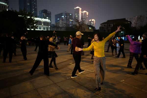 Люди танцуют ночью парке спустя год после вспышки COVID-19 в Ухане - Sputnik Latvija
