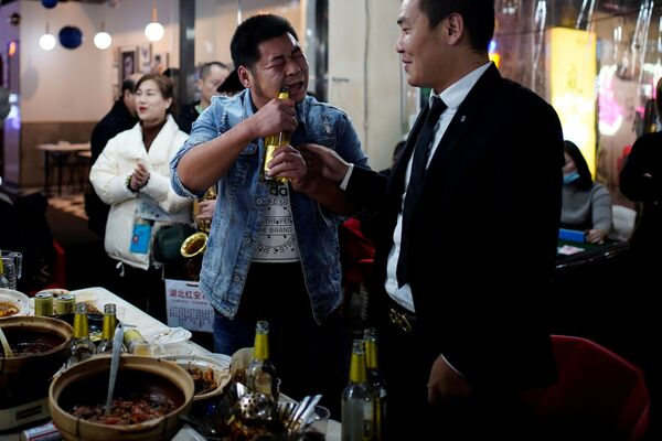 Мужчина открывает пиво зубами в одном из ресторанов Уханя - Sputnik Latvija