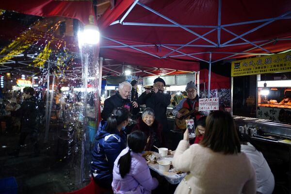 Посетители в уличном ресторане ночью в Ухане - Sputnik Latvija