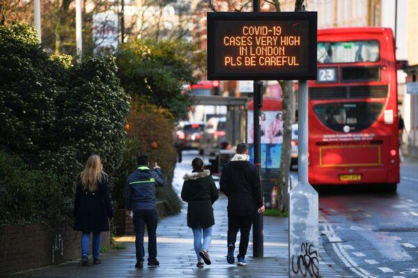 Табличка с сообщением об ограничениях в связи с COVID на улице Лондона - Sputnik Latvija