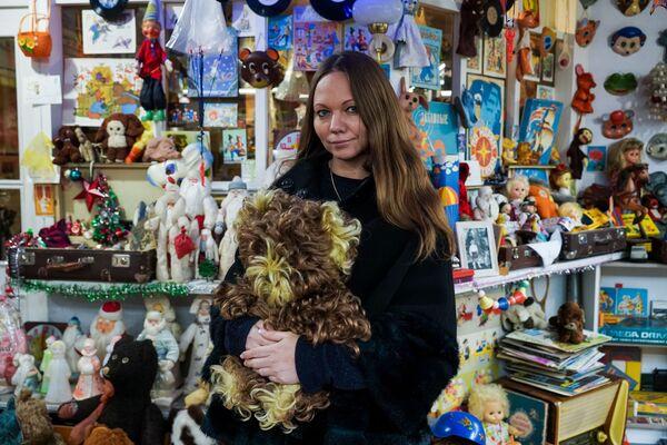 Muzeja Mūsu bērnība saimniece Jana Voronova ar pieturā  atrastu lāci - Sputnik Latvija