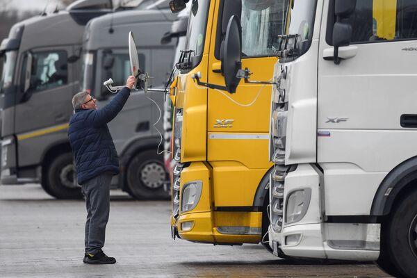 Ungāru tālbraucējs regulē kravas auto antenu stāvvietā Lielbritānijā - Sputnik Latvija