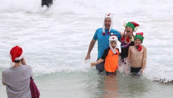 Люди в рождественской одежде позируют для фотографий в Рождество на пляже Бонди в Сиднее, Австралия - Sputnik Латвия