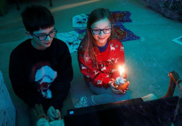 Дети во время онлайн-служения Christingle в канун Рождества в Блэксли, Великобритания - Sputnik Latvija