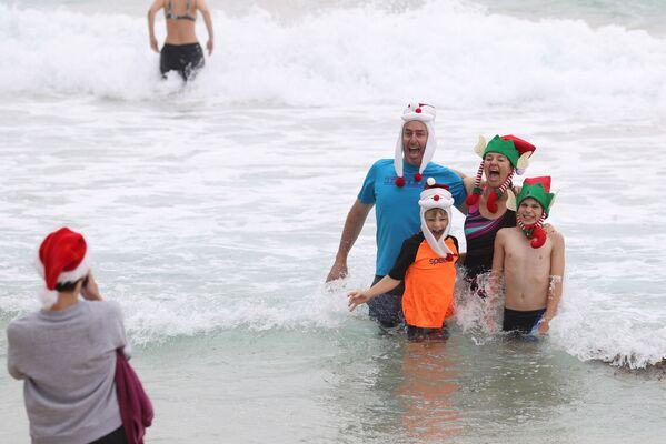Люди в рождественской одежде позируют для фотографий в Рождество на пляже Бонди в Сиднее, Австралия - Sputnik Latvija