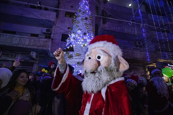 Мужчина в костюме Санта-Клауса во время празднования Рождества в сирийском городе Эль-Камышлы - Sputnik Latvija