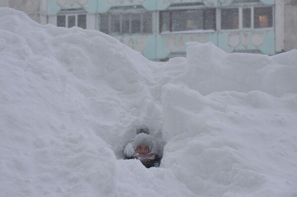 Ребенок играет в сугробе во дворе жилого дома в Норильске - Sputnik Latvija