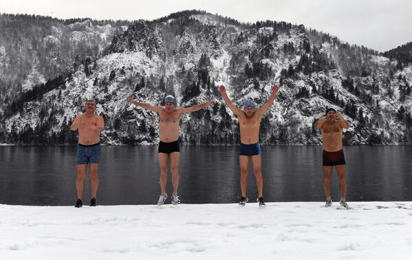 Члены клуба зимнего плавания Дельфин разминаются на набережной перед купанием на реке Енисей в Дивногорске - Sputnik Latvija