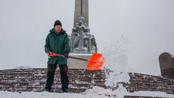 Мужчина убирает снег у памятника Свободы в Риге - Sputnik Латвия