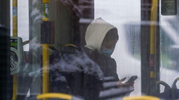 Женщина в маске в общественном транспорте в Риге - Sputnik Latvija