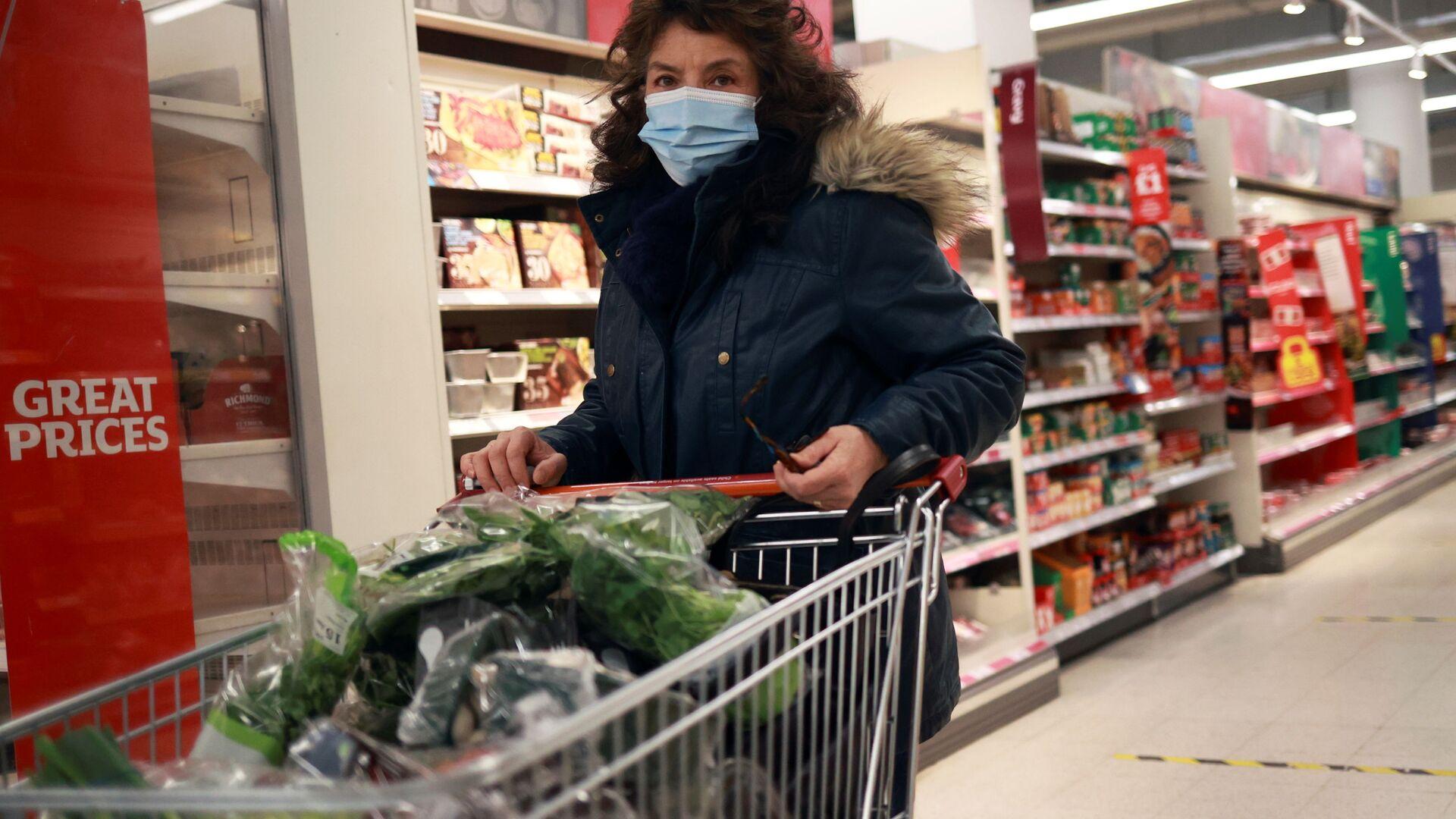 Женщина в защитной маске в супермаркете - Sputnik Латвия, 1920, 28.09.2021