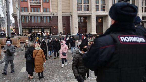 Сотрудник полиции и люди на Манежной площади в Москве во время несанкционированной акции сторонников Алексея Навального. - Sputnik Latvija