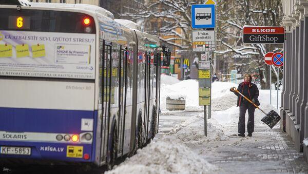Женщина убирает снег на остановке общественного транспорта - Sputnik Латвия