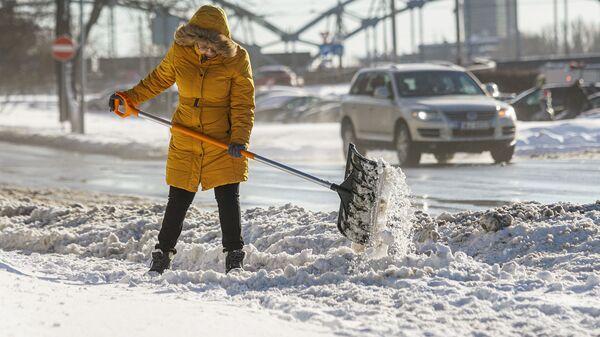 Женщина убирает снег - Sputnik Латвия