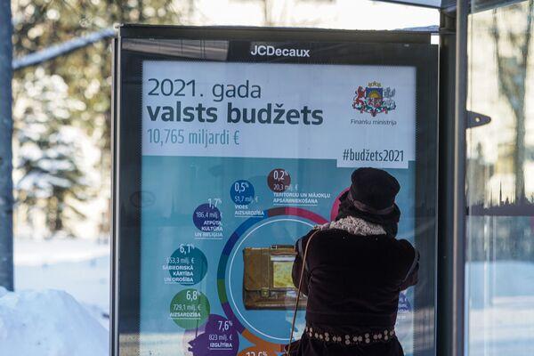 Информационный плакат на остановке общественного транспорта о расходах латвийского бюджета в 2021 году - Sputnik Латвия