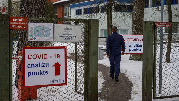 Мужчина направляется в пункт приема тестов на COVID-19 в Латвийском центре инфектологии - Sputnik Латвия