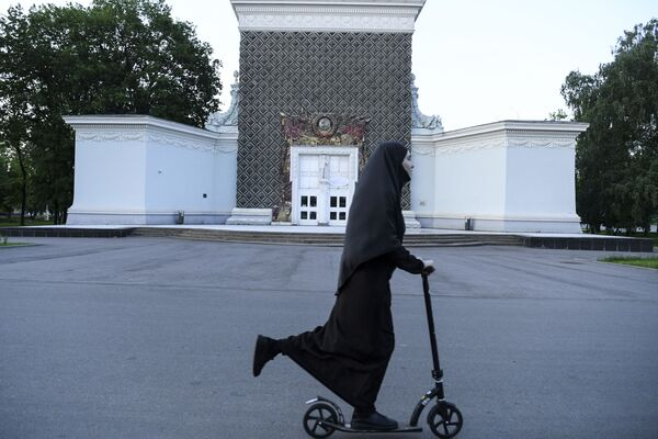 Женщина в хиджабе катается на скутере перед зданием с символикой Советского Союза во Всероссийском выставочном центре в Москве - Sputnik Latvija