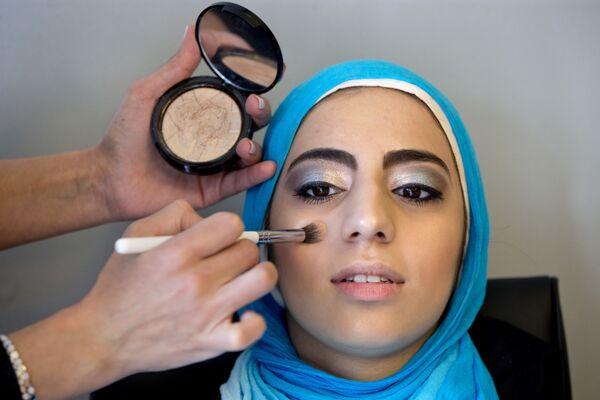 Молодая девушка в хиджабе делает макияж, готовясь к выпускному вечеру в старшей школе в Джермантуане, США - Sputnik Latvija