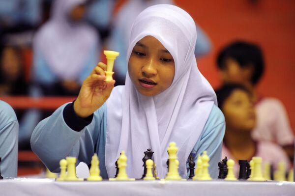 Молодая девушка в хиджабе принимает участие в показательной игре в шахматы в гимназии в Джакарте - Sputnik Latvija