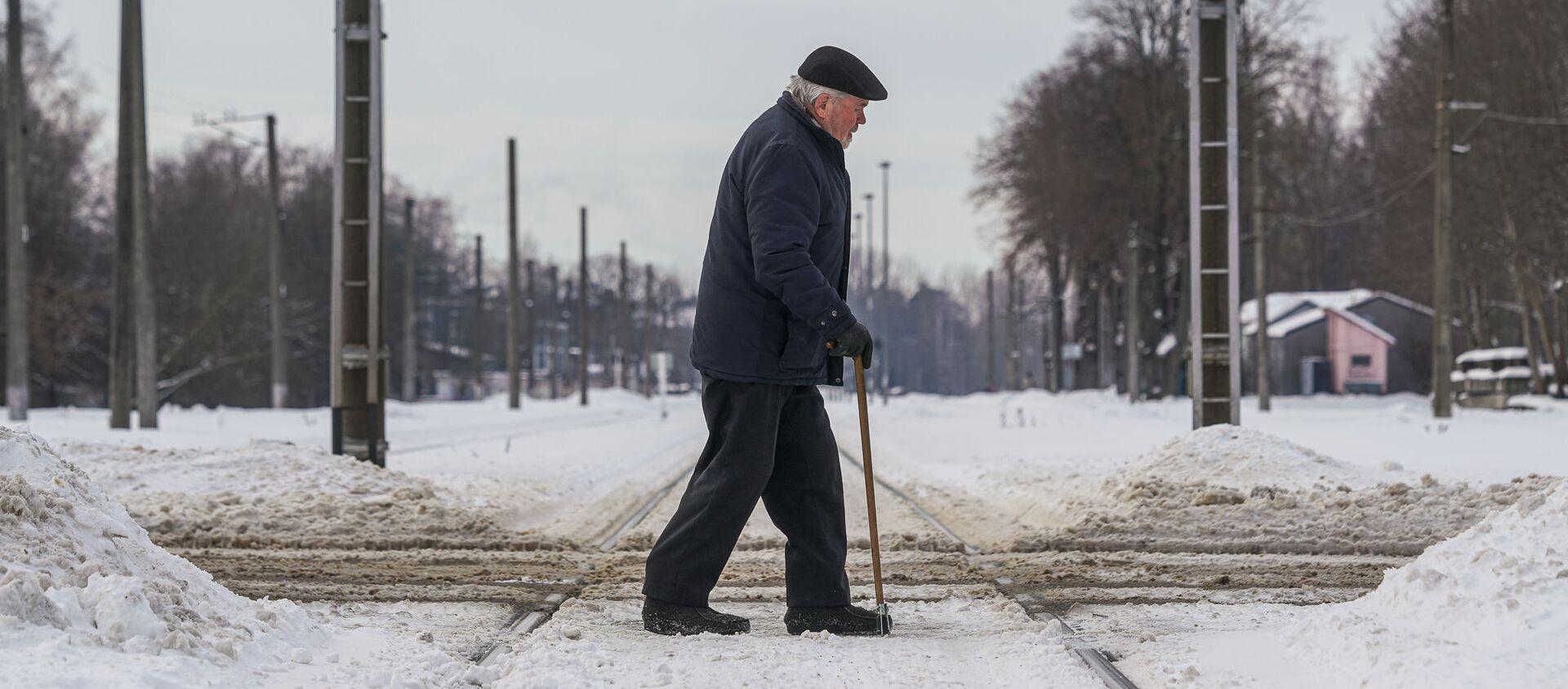 Пожилой мужчина переходит через железнодорожные пути - Sputnik Латвия, 1920, 10.02.2021