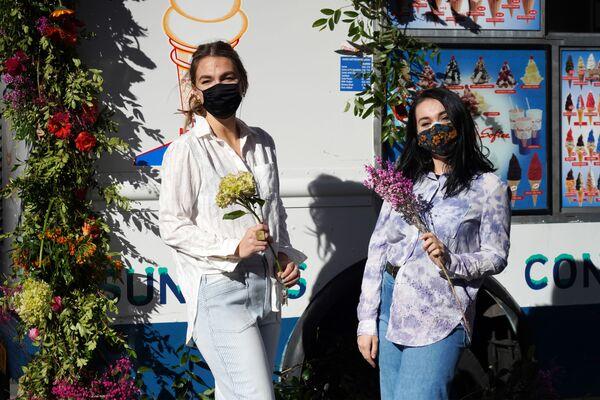 Девушки с букетами на Рокфеллер Плаза в преддверии Дня святого Валентина в Нью-Йорке, США - Sputnik Latvija