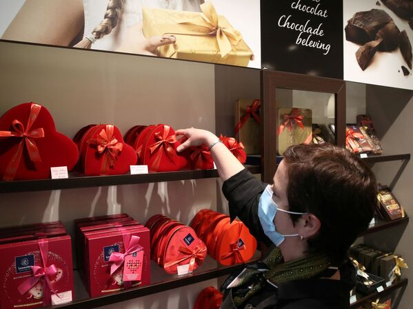 Продавец одного из самых престижных производителей шоколада Бельгии расставляет коробки во время подготовки ко Дню святого Валентина в Брюсселе, Бельгия - Sputnik Latvija