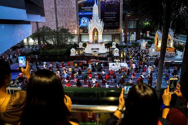 Люди молятся во время религиозной церемонии в храме Пхра Тримурти, Богу любви, чтобы пожелать удачи в поисках родственных душ в преддверии Дня святого Валентина в торговом районе Бангкока, Таиланд - Sputnik Latvija