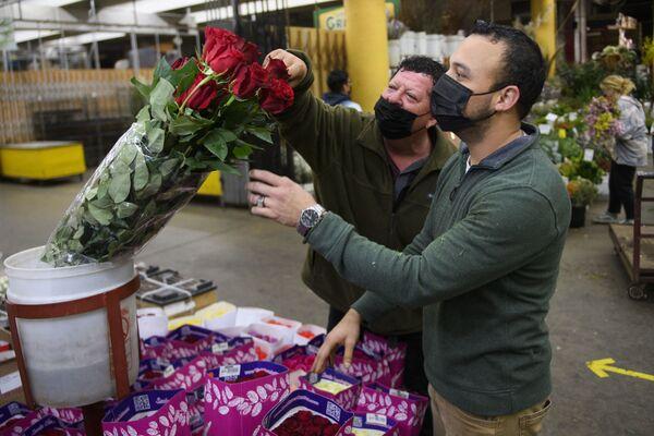 Торговец помогает выбрать букет покупателю в преддверии Дня святого Валентина на цветочном рынке в Лос-Анджелесе, Калифорния - Sputnik Latvija